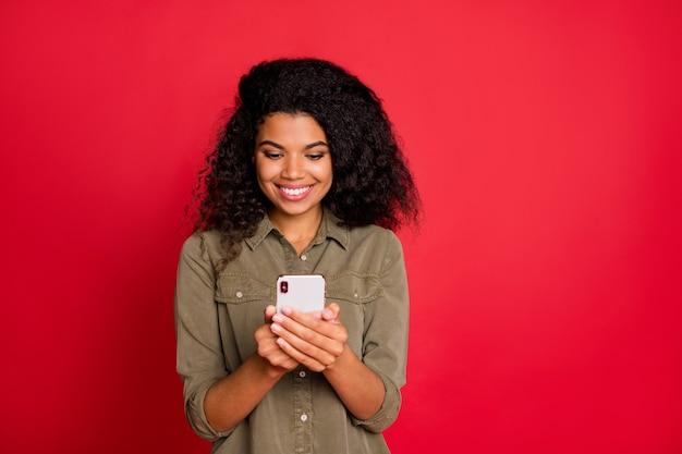 Vrolijke positieve schattige vrij aardige jongere bladeren door haar smartphone op zoek naar nieuwe geïsoleerde informatie