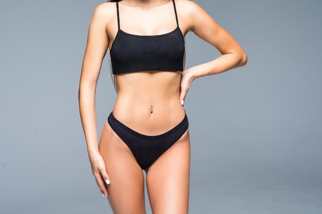 Vrolijke positieve sexy fit vrouw in lingerie wijst naar haar slanke buik. vrouw toont haar platte buik, ideale taille, vrouw opscheppen over haar gewicht. geïsoleerde witte muur, fitness, sport