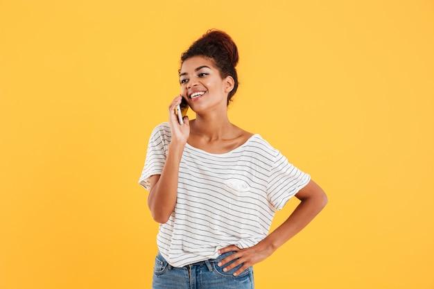 Vrolijke positieve vrouw die op geïsoleerde telefoon spreekt