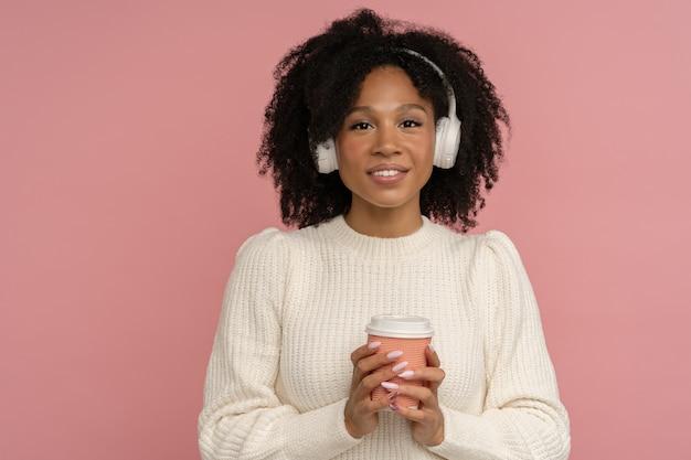 Vrolijke positieve vrouw met koptelefoon, papieren kopje warme koffie of thee afhaalmaaltijden te houden