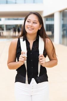 Vrolijke positieve vrouwelijke toerist die buiten loopt