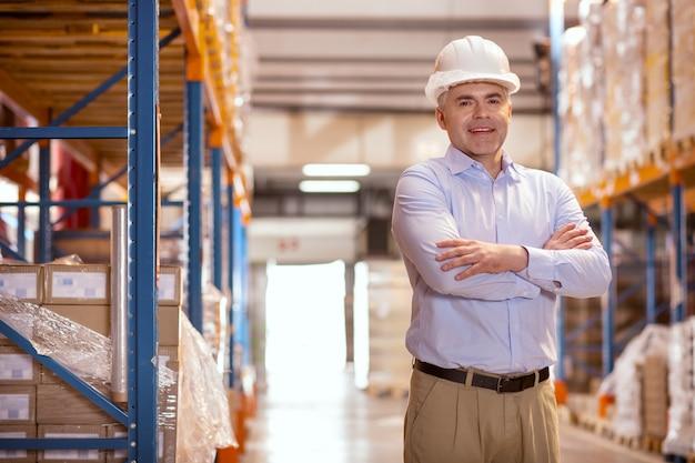 Vrolijke positieve zakenman glimlachen terwijl hij tevreden is over zijn bedrijf