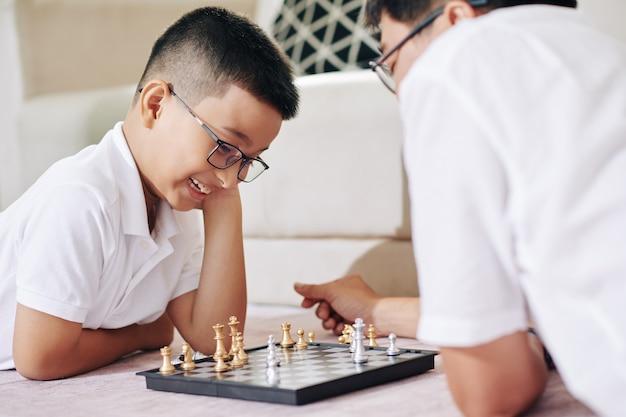 Vrolijke preteen aziatische jongen in glazen na te denken over de volgende zet bij het spelen van een spelletje schaak met zijn vader
