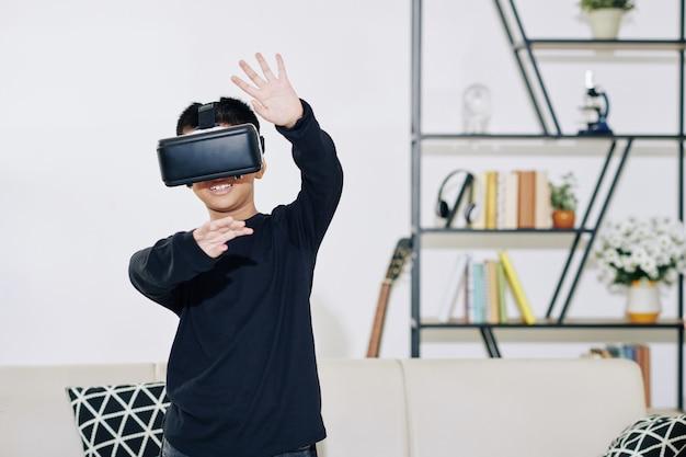 Vrolijke preteen jongen in virtual reality headset genieten van het spelen van videogame thuis