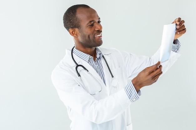 Vrolijke professionele arts die een röntgenscan houdt terwijl hij blijheid uitdrukt