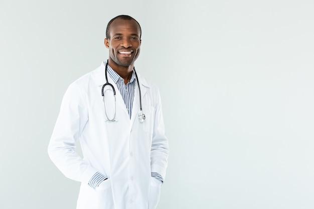 Vrolijke professionele arts hand in hand in de zakken tijdens het glimlachen