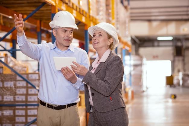 Vrolijke professionele managers die samenwerken terwijl ze in het magazijn zijn