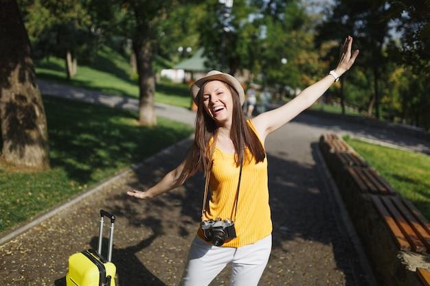 Vrolijke reiziger toeristische vrouw in hoed met koffer retro vintage fotocamera spreidende handen als vleugels in de stad buiten. meisje dat naar het buitenland reist om een weekendje weg te reizen. toeristische reis levensstijl.