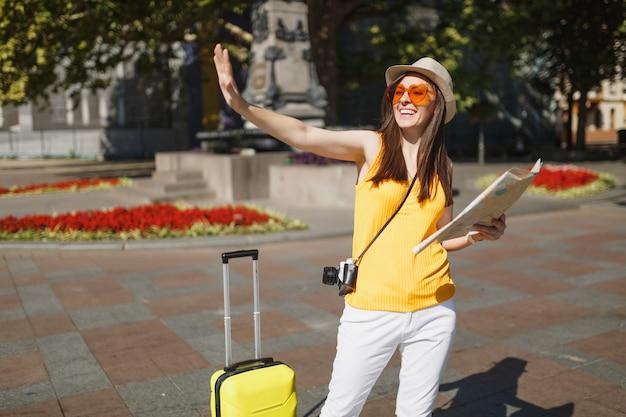 Vrolijke reiziger toeristische vrouw in oranje hart bril met koffer stadskaart zwaaiende hand voor begroeting, ontmoet vriend in de stad buiten. meisje op weekendje weg naar het buitenland. toeristische reis levensstijl.