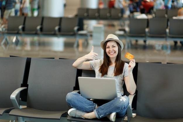 Vrolijke reiziger toeristische vrouw met laptop zittend met gekruiste benen, duim omhoog houden creditcard wacht in lobby hal op luchthaven