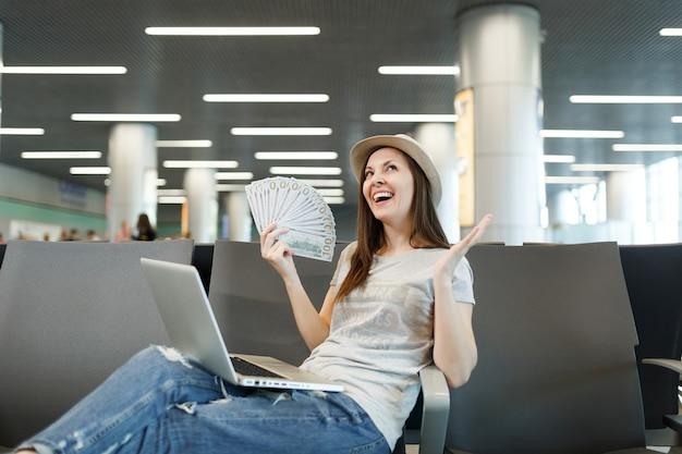 Vrolijke reizigerstoeristenvrouw die op laptop werkt, een bundel dollars contant geld vasthoudt, handen spreidt, wacht in de lobby op de luchthaven