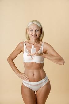 Vrolijke rijpe blonde vrouw in ondergoed met een fit lichaam dat naar de camera glimlacht en reclame vasthoudt