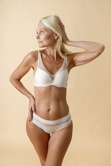 Vrolijke rijpe blonde vrouw met perfecte lichaamsvorm in wit ondergoed die opzij kijkt om haar aan te raken