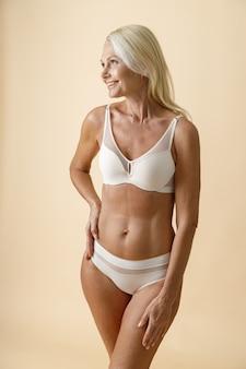 Vrolijke rijpe blonde vrouw met perfecte lichaamsvorm in wit ondergoed glimlachend opzij hand in hand?