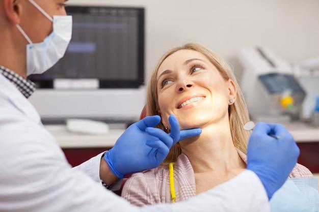 Vrolijke rijpe vrouw die bij haar tandarts tijdens algemeen medisch onderzoek glimlacht