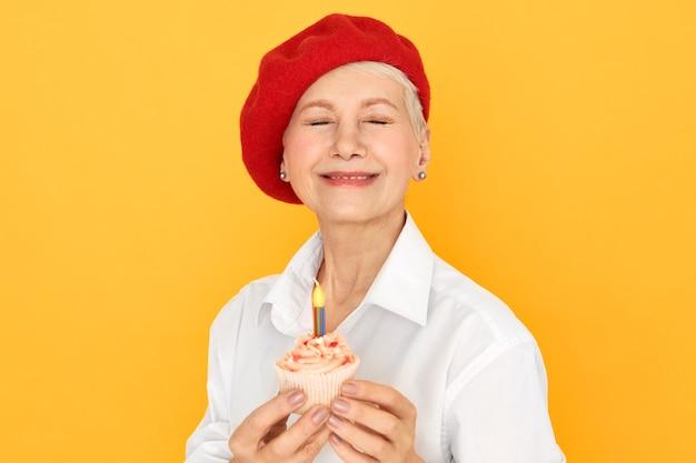 Vrolijke rijpe vrouw die elegante rode motorkap sluitende ogen draagt tijdens het maken van wens op haar verjaardag