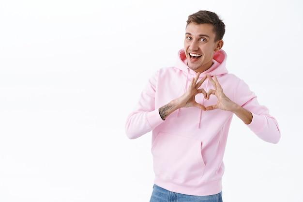 Vrolijke romantische blonde man betuigt zijn medeleven, feliciteert minnaar met verjaardag, toont hartteken als bekennen in liefde en tedere gevoelens, vrolijk glimlachend, staande witte muur