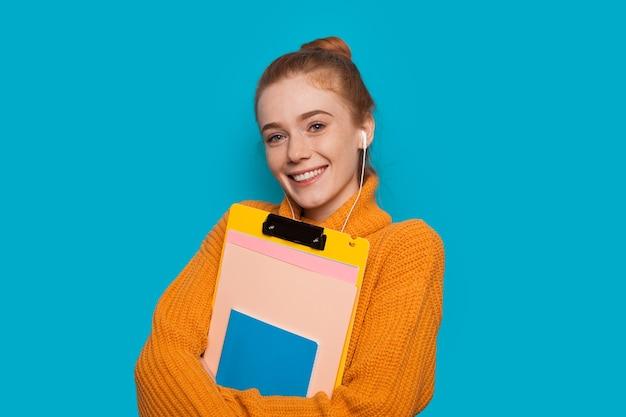 Vrolijke roodharige blanke student met sproeten houdt enkele boeken vast en poseren op een blauwe muur
