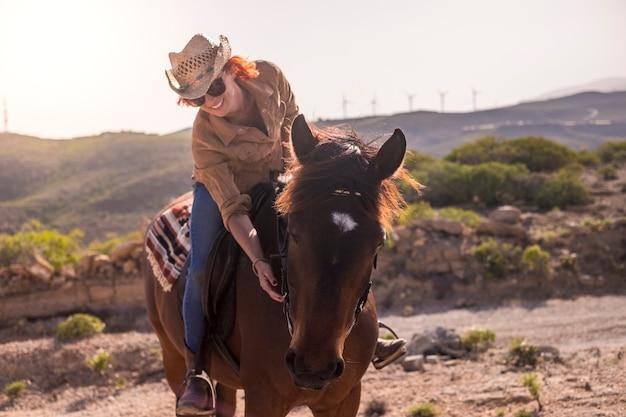 Vrolijke roodharige dame rijdt in vriendschap op een mooi bruin paard en geniet samen van de buitendag. relatie- en huisdiertherapie. gelukkige en vreugdevolle levensstijl in contact met de natuur