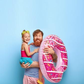 Vrolijke roodharige familie heeft plezier aan de kustlijn. tevreden vrolijke bebaarde vader houdt een klein meisje en een opgeblazen zwemring vast