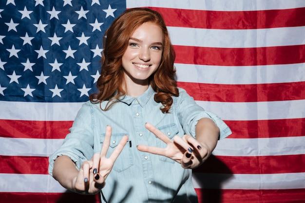 Vrolijke roodharige jonge dame die vredesgebaar toont.