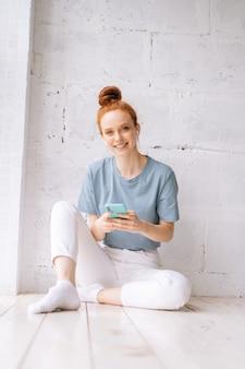 Vrolijke roodharige jonge vrouw die draadloze oortelefoons draagt en ontspannen muziek luistert met behulp van mobiele telefoon