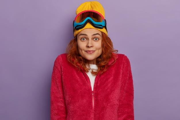 Vrolijke roodharige jongedame draagt warme kleren, skibril op het hoofd, vormt tegen paarse achtergrond.