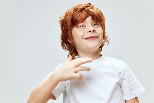 Vrolijke roodharige jongen gebaren met de emotie van de handglimlach