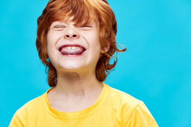 Vrolijke roodharige kind bijt tong emoties geel t-shirt leuke blauwe geïsoleerde achtergrond