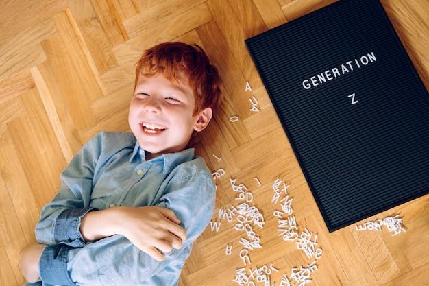 Vrolijke roodharige kleine jongen met een bord met de tekst