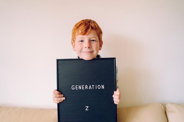 Vrolijke roodharige kleine jongen met een schoolbord met tekst