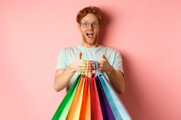 Vrolijke roodharige man die geschenken koopt, boodschappentassen vasthoudt en glimlacht, staande over roze achtergrond.