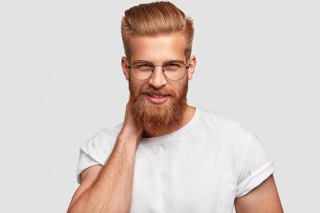 Vrolijke roodharige man met dikke baard en snor, kijkt mysterieus door een bril, draagt casual shirt
