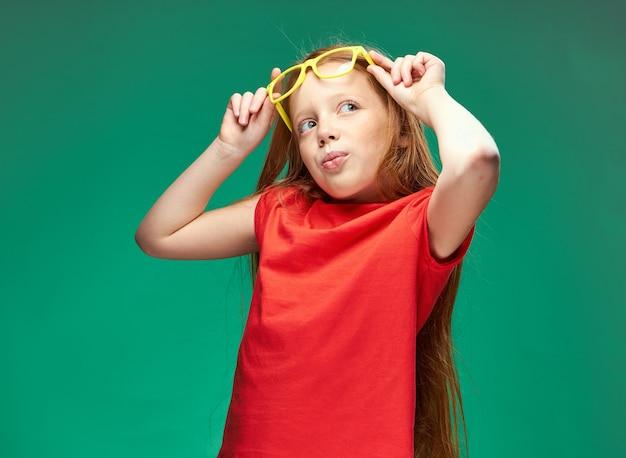 Vrolijke roodharige meisje met bril in haar handen leren school groene achtergrond