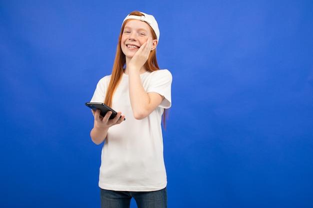 Vrolijke roodharige tiener meisje in een wit t-shirt communiceert op sociale netwerken vanaf een smartphone op een blauw