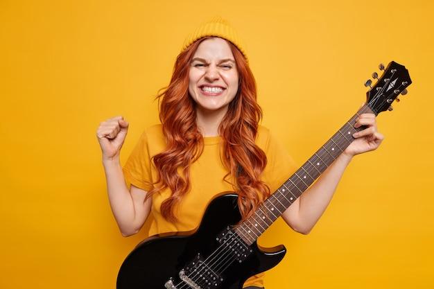 Vrolijke roodharige vrouw balt vuist met triomf blij dat veel fans rockmuziek spelen op elektrische gitaar draagt hoed en t-shirt