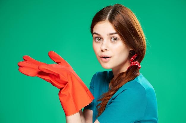 Vrolijke roodharige vrouw die rubberhandschoenen draagt ?? huis schoonmakende beroeps