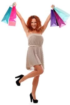 Vrolijke roodharige vrouw met boodschappentassen