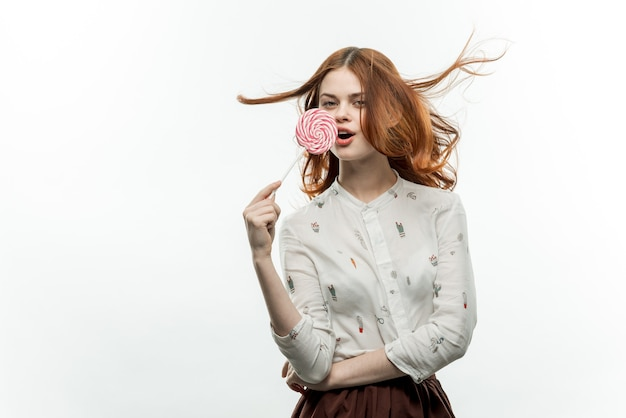 Vrolijke roodharige vrouw met een lolly in haar handen emoties open mond snoep
