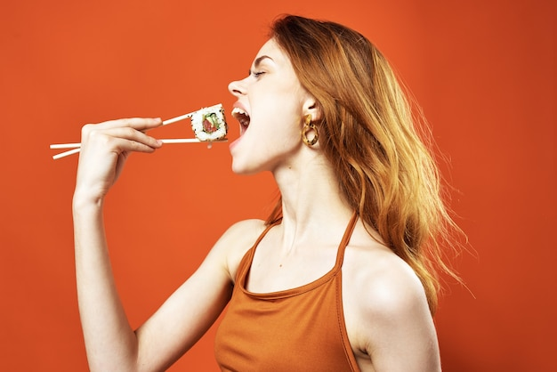 Vrolijke roodharige vrouw sushi rolt dieet leuk close-up