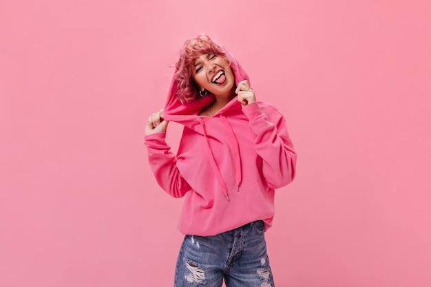 Vrolijke rozeharige vrouw in fuchsia hoodie en denim shorts demonstreert tong en maakt een grappig gezicht op geïsoleerde muur