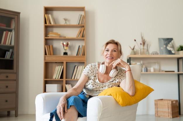 Vrolijke rustgevende vrouw van middelbare leeftijd in homewear en koptelefoon zitten in witte lederen comfortabele fauteuil thuis