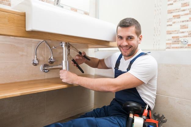Vrolijke sanitaire technicus op het werk