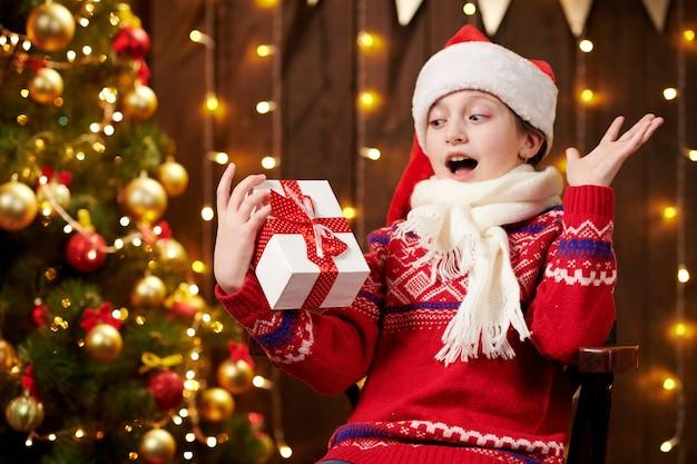 Vrolijke santa helper meisje met geschenkdoos zit binnen in de buurt van dec