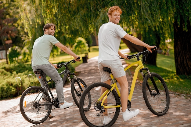 Vrolijke schattige bebaarde jonge sportman en zijn blije gembervriend die 's ochtends samen fietsen
