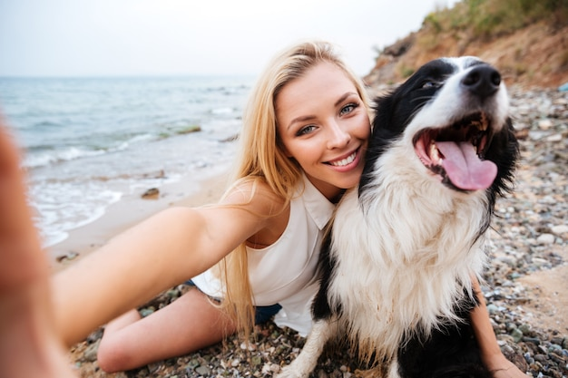 Vrolijke schattige jonge vrouw die selfie met hond op het strand neemt