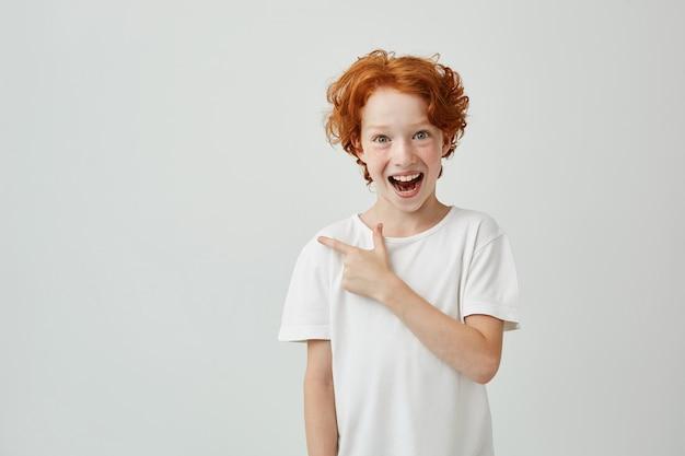 Vrolijke schattige kleine jongen met krullend gember haar en sproeten gelukkig lachend en opzij wijzen met de vinger. kopieer ruimte.