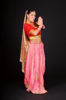 Vrolijke schattige volwassen vrouw vormt in traditionele indiase kostuum. geïsoleerd op donkere achtergrond