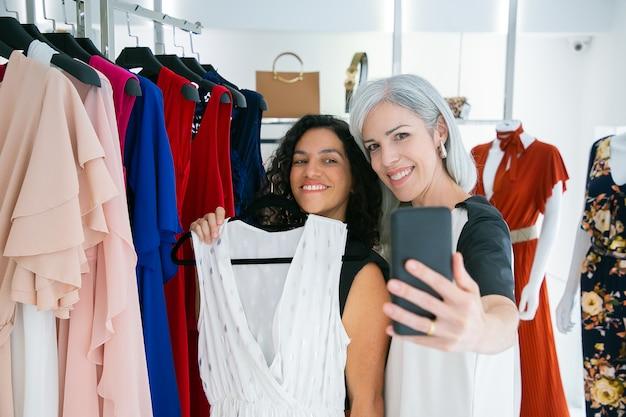 Vrolijke schattige vriendinnen genieten van winkelen in boetiek samen, jurk houden, plezier hebben en selfie op mobiele telefoon te nemen. consumentisme of winkelconcept