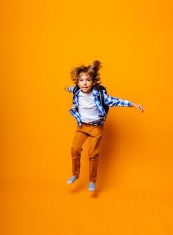 Vrolijke schooljongen in een rugzak die op een gele achtergrond springt. dynamische afbeeldingen. terug naar school.